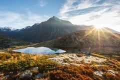 野营与在高处湖附近的帐篷阿尔卑斯的 积雪覆盖的山脉和风景五颜六色的天空的反射在日落 库存图片