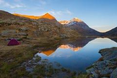 野营与在高处湖附近的帐篷阿尔卑斯的 积雪覆盖的山脉和风景五颜六色的天空的反射在日落 免版税图库摄影