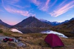 野营与在高处湖附近的帐篷阿尔卑斯的 积雪覆盖的山脉和风景五颜六色的天空的反射在日落 免版税库存图片
