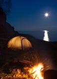 野营与篝火的游人在晚上 免版税库存照片