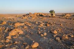 野营与4x4和在安哥拉` s纳米比亚沙漠的一个岩石部分的屋顶顶面帐篷 免版税库存照片