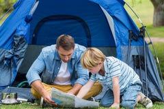 野营和寻找他们的方式家的父亲和儿子 图库摄影
