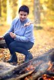 野营在一顿野餐的森林美丽的成熟妇女在森林A妇女是烹调在火的烟肉,串起在棍子 库存照片