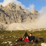 野营在与壮观的风景的山的人们 图库摄影