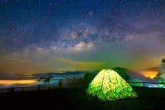 野营在与有启发性帐篷的星下,银河星系,长的曝光照片,与五谷 图象包含某一五谷 免版税库存图片