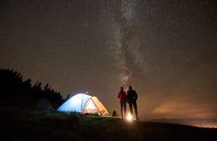 野营在山的夜夏天在夜满天星斗的天空下 免版税库存图片
