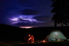 野营在山的夜 夫妇游人有休息在营火近有启发性帐篷 图库摄影