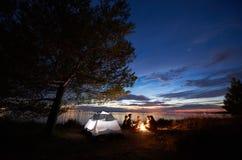 野营在岸的夜夏天 小组在营火附近的年轻游人在帐篷附近在晚上天空下 免版税库存图片