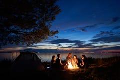 野营在岸的夜夏天 小组在营火附近的年轻游人在平衡天空下的帐篷附近 免版税库存照片