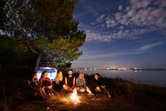 野营在岸的夜夏天 小组在营火附近的年轻游人在平衡天空下的帐篷附近 免版税库存图片