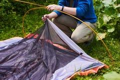 野营在帐篷-设置在野营的游人一个帐篷 人` s手的关闭在森林里时拿着一个帐篷,当设定一个帐篷 免版税库存图片