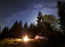 野营在旅游帐篷附近的男性远足者enjoyng夜在营火在蓝色满天星斗的天空和银河下 免版税库存图片