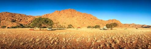 野营在有卡车和帐篷的沙漠 日落晚上 免版税库存图片