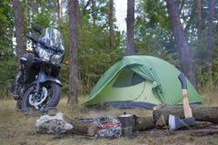 野营在有帐篷和摩托车的森林 库存照片