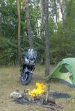 野营在有帐篷和摩托车的森林 免版税库存照片
