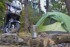 野营在有帐篷和摩托车的森林 免版税库存图片