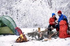 野营在有帐篷和火的森林里的冬天 免版税库存图片