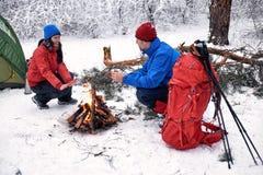 野营在有帐篷和火的森林里的冬天 库存图片