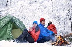 野营在有帐篷和火的森林里的冬天 库存照片