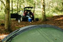 野营在有汽车的一个森林地 免版税库存照片