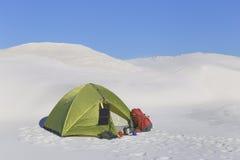 野营在有背包和帐篷的沙漠 图库摄影