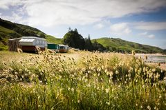 野营在有蓬卡车的自由在一个东海岸海滩,吉斯伯恩,北岛,新西兰 免版税图库摄影
