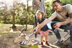野营在森林里的家庭,烹调在烤肉格栅的肉 免版税库存图片