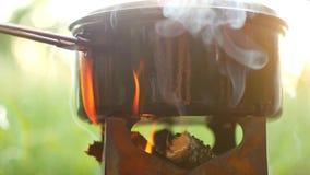 野营在森林A罐食物在火炉煮沸 烟来自火 股票视频