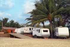 野营在海滩的有蓬卡车在棕榈下 图库摄影