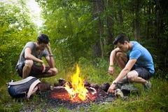 野营在灼烧的营火旁边的两个年轻人 免版税库存照片