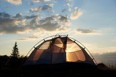 野营在破晓 帐篷站立在与云彩的蓝天下在早晨阳光光芒  库存照片