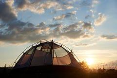 野营在破晓 帐篷站立在与云彩的蓝天下在晚上阳光光芒  免版税库存图片