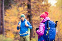 野营在秋天森林里的男人和妇女愉快的夫妇远足者 免版税库存照片