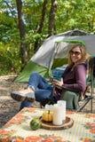 野营在秋天的愉快的妇女帐篷拿着一个杯子咖啡在早晨 库存照片