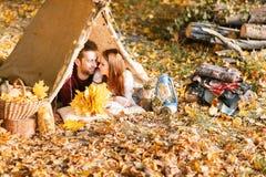 野营在秋天自然的男人和妇女远足者 野营在帐篷的愉快的年轻夫妇背包徒步旅行者 库存图片