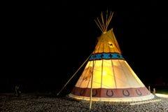 野营在美国人第一个国家传统圆锥形帐蓬在晚上 库存图片