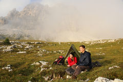 野营在雾的山的青年人 库存图片