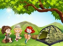 野营在领域的三个女孩 免版税库存照片