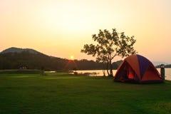野营地和日落在湖 库存图片
