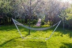 野营的关闭的柳条吊床-在开花的春天庭院背景在一个晴天 免版税库存照片