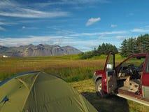 野营的冒险在冰岛-帐篷和老越野汽车有操作的 库存照片