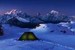 野营的冬天,夜,在雪的发光的绿色帐篷 夜射击,长的曝光,睡觉在雪在户外 阿尔卑斯hochries山景 免版税图库摄影
