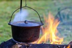 野营的厨具-在火的罐在一个室外露营地 免版税库存照片
