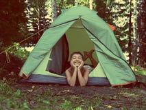 野营的帐篷的-葡萄酒减速火箭的样式愉快的男孩 免版税库存图片
