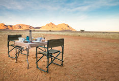 野营的桌和椅子在沙漠 巨大视图 日出 库存照片