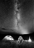 野营的游人在反对满天星斗的天空的晚上 免版税图库摄影