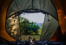 野营 在帐篷的早晨 在一个绿色帐篷的女性腿 库存图片