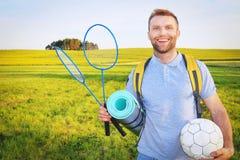 野餐与背包,球拍badbotton的和球的一个年轻秀丽人微笑反对一个绿色草甸的背景 免版税库存照片
