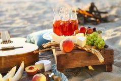 去野餐在海滩在日落用果子和汁液 免版税库存照片