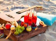 去野餐在海滩在boho样式的日落 库存照片